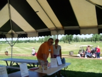 Memorial Regional Health Golf Outing event staff standing behind a table inside of a tent on the golf course to provide information to players